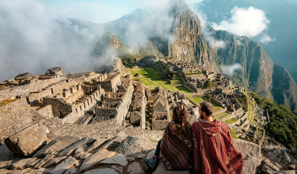 Image of a couple sitting at a lookout overlooking Machu Picchu in Peru.